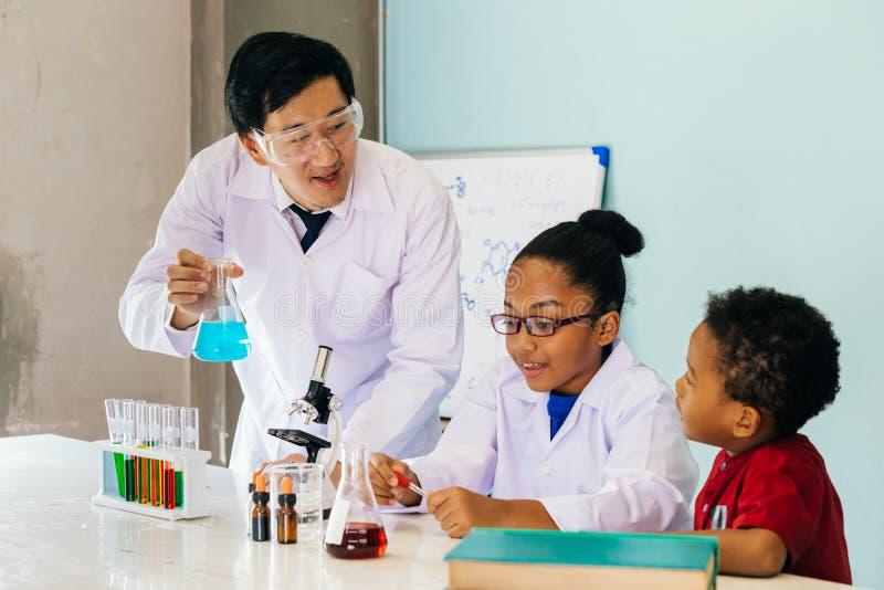 拿着烧瓶和教两个非裔美国人的混杂的孩子的年轻科学家在化学实验室 免版税库存照片