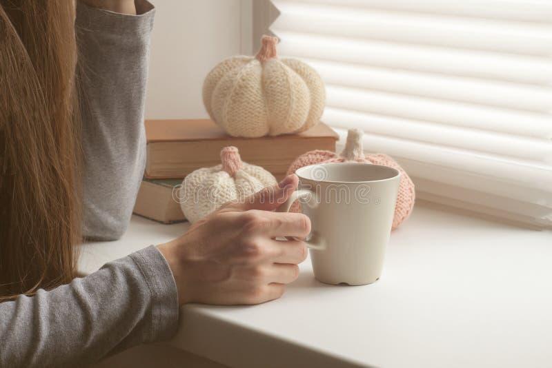 拿着热的咖啡或茶在早晨阳光下的手,喝热的饮料的美丽的浪漫无法认出的女孩在舒适h 库存照片