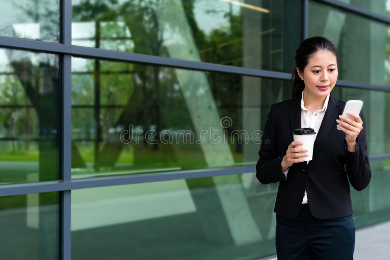 拿着热的咖啡杯的甜办公室工作者女孩 图库摄影