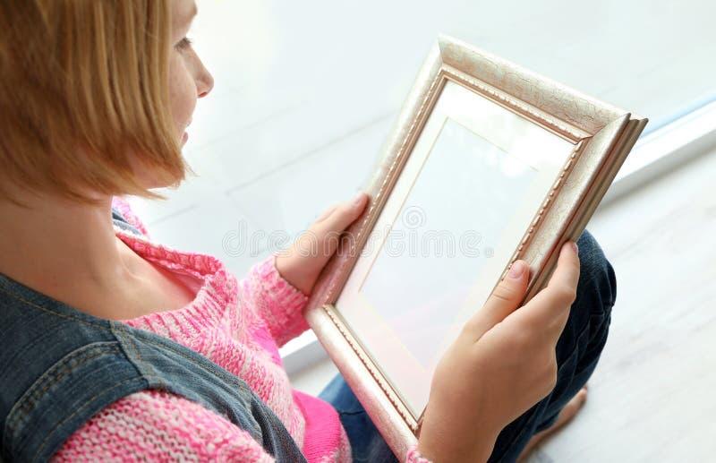 拿着照片框架和坐在窗口附近的少年女孩 图库摄影