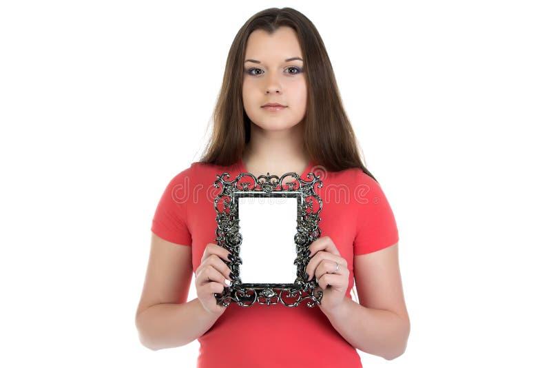 拿着照片框架的十几岁的女孩画象 免版税库存照片