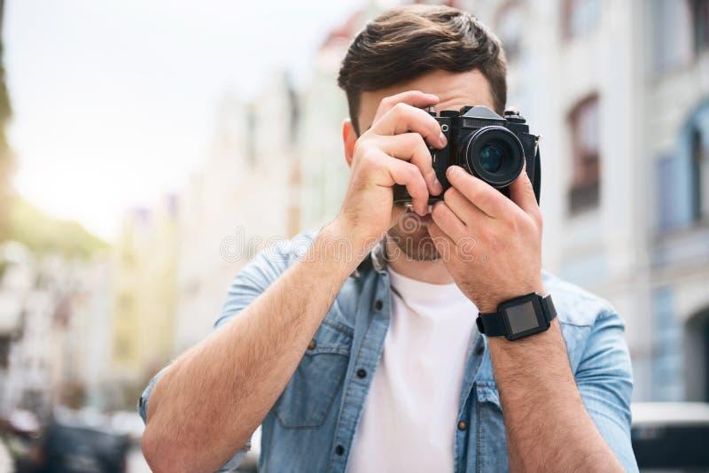 拿着照片照相机的宜人的快乐的人 免版税库存照片
