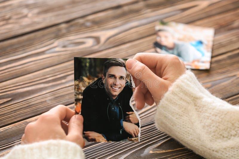 拿着照片的被撕毁的部分与她的前夫的妇女 离婚的概念 库存图片