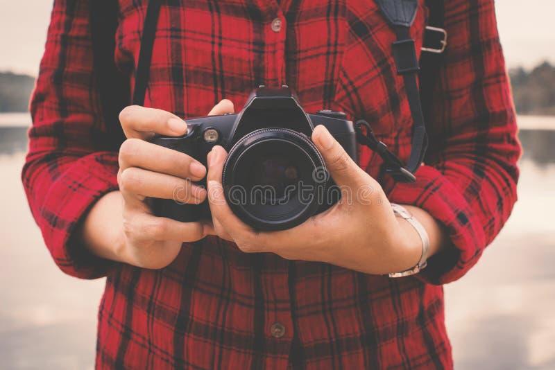 拿着照相机和享用本质上的女性手特写镜头 免版税库存图片