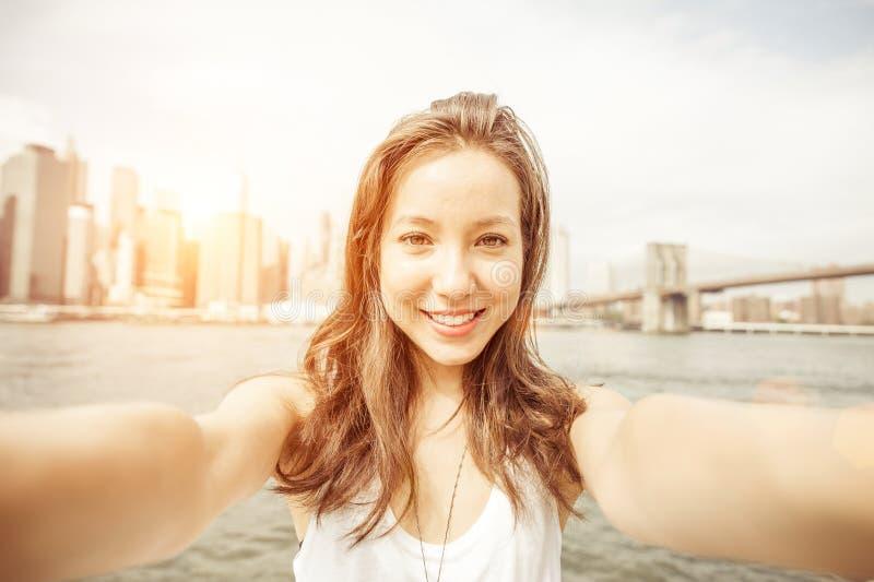 拿着照相机和采取自画象的美丽的亚裔女孩在纽约 免版税库存图片