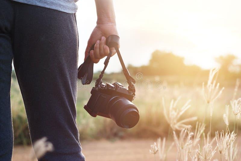 拿着照相机的妇女手中在日落自然背景 图库摄影