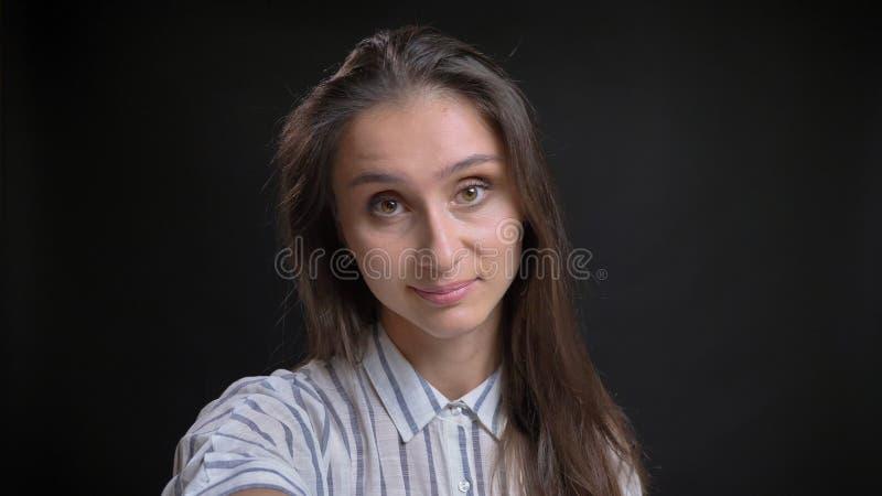 拿着照相机的年轻可爱的女性特写镜头射击看直接和采取愉快地微笑与的selfie 免版税库存照片