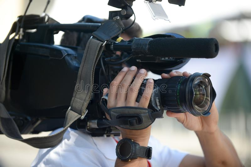 拿着照相机的摄影师在街道上的采访中 免版税图库摄影
