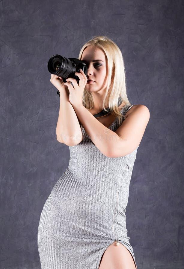 拿着照相机的灰色礼服的年轻白肤金发的妇女 做图片的摄影师 免版税库存图片