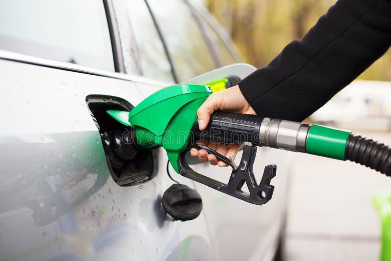 拿着燃油泵和重新装满汽车的手特写镜头照片在加油站 免版税库存照片