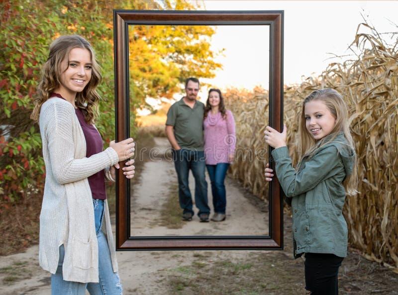拿着父母的画框姐妹 免版税库存照片