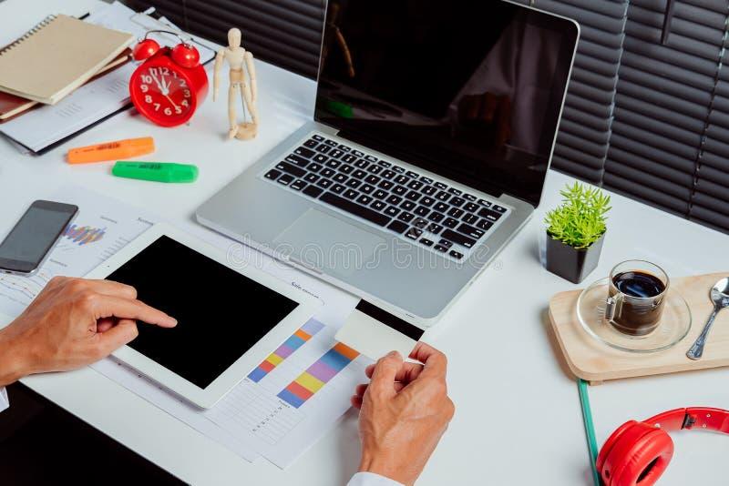 拿着片剂个人计算机和信用卡的人 免版税图库摄影