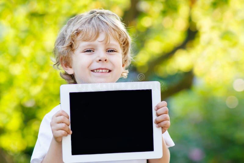 拿着片剂个人计算机的微笑的愉快的小孩,户外 免版税库存图片