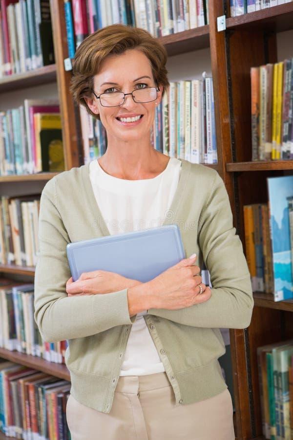 拿着片剂个人计算机的老师在图书馆 免版税库存图片