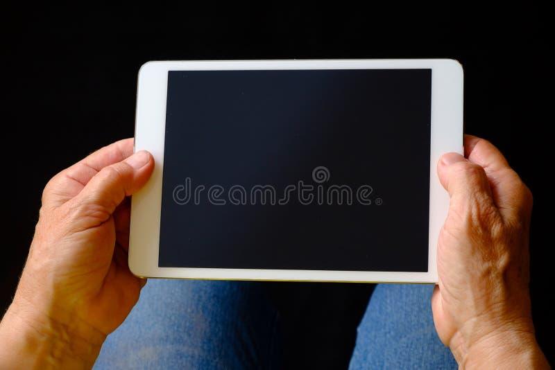拿着片剂个人计算机的资深妇女的手 库存图片