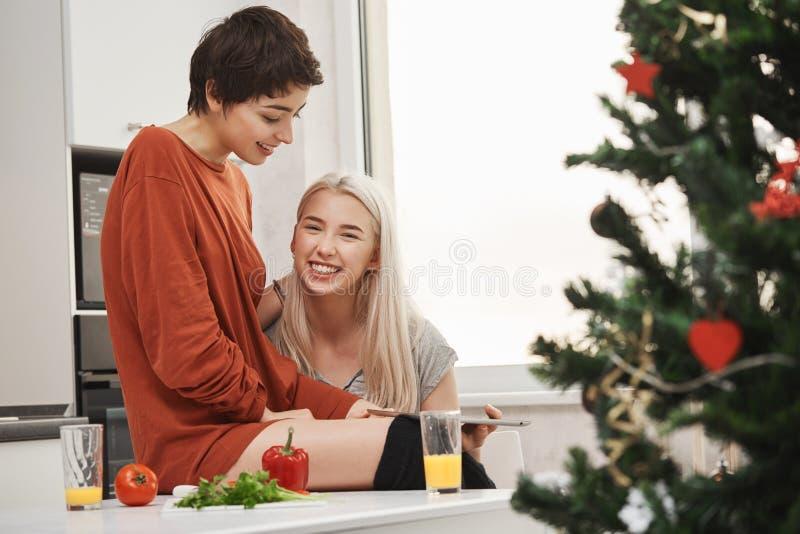 拿着片剂和微笑对照相机的愉快的可爱的白肤金发的女孩,当坐在她可爱的女朋友旁边在厨房里时 图库摄影