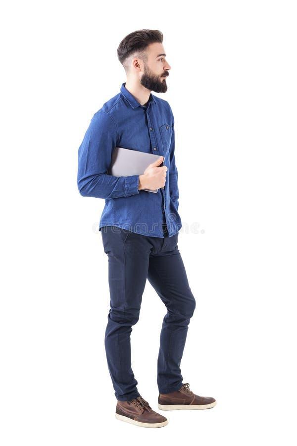 拿着片剂的凉快的轻松的有胡子的商人侧视图看用在口袋的手 免版税图库摄影