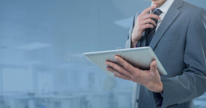 拿着片剂的商人在蓝色车间工厂办公室 免版税库存图片