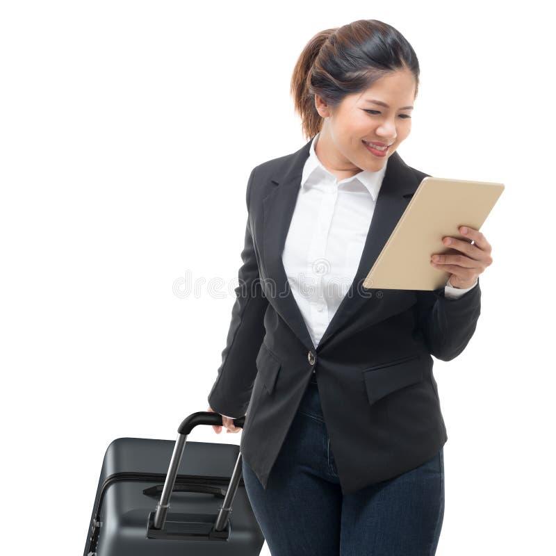 拿着片剂的女实业家手,当运载行李时 免版税库存照片