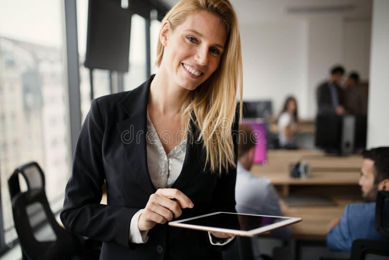拿着片剂的美丽的白肤金发的女实业家画象  免版税图库摄影