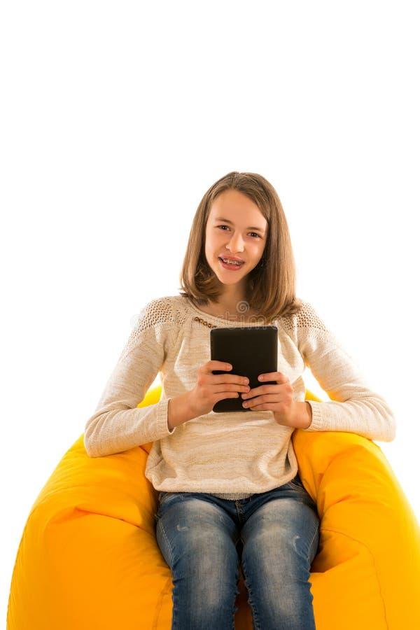 拿着片剂的年轻微笑的女孩,当坐黄色是时 库存图片