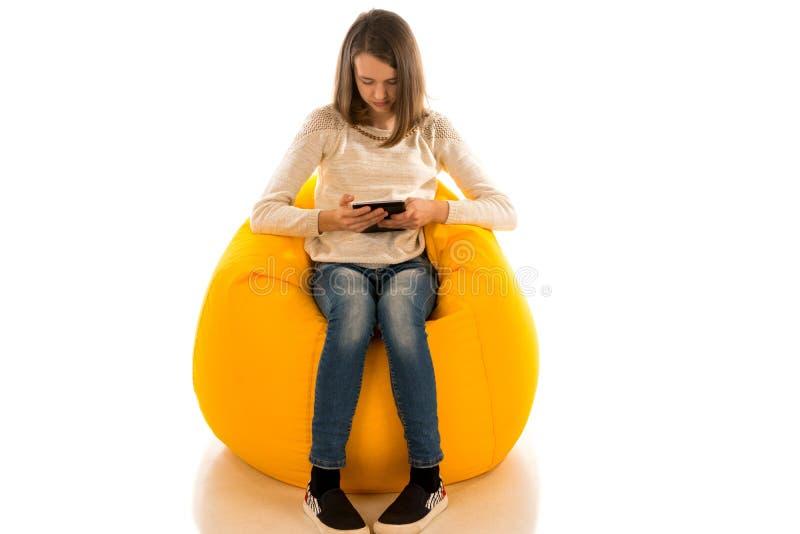 拿着片剂的年轻逗人喜爱的女孩,当坐黄色beanb时 免版税库存图片