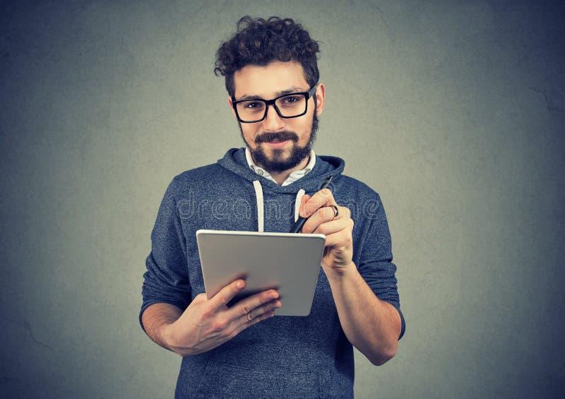 拿着片剂计算机和笔的玻璃的Hispter人看照相机 免版税图库摄影