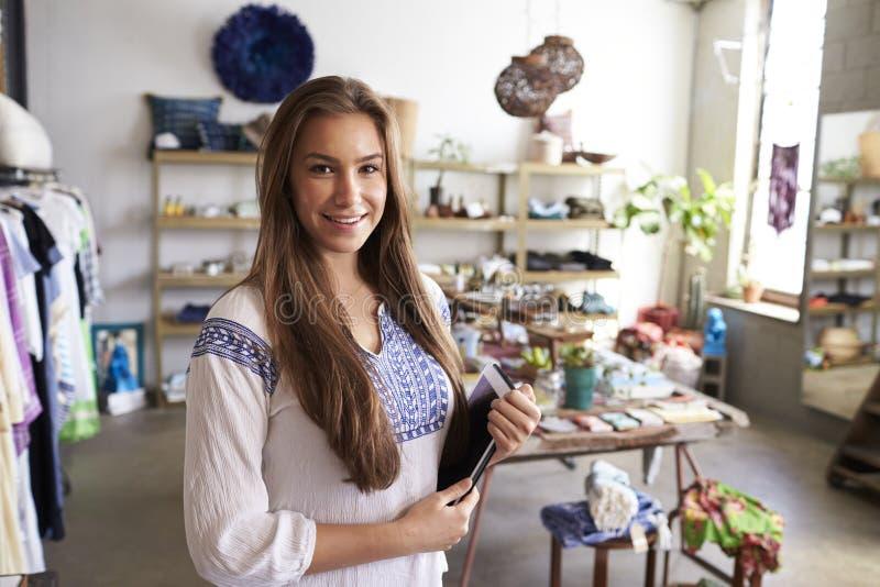 拿着片剂计算机的女性精品店经理在商店 免版税库存照片