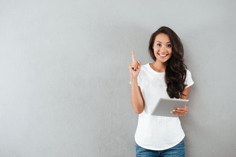 拿着片剂计算机的激动的愉快的亚裔妇女 免版税图库摄影