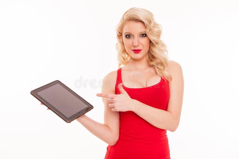 拿着片剂comp的红色T恤杉的美丽的年轻白肤金发的妇女 免版税库存照片