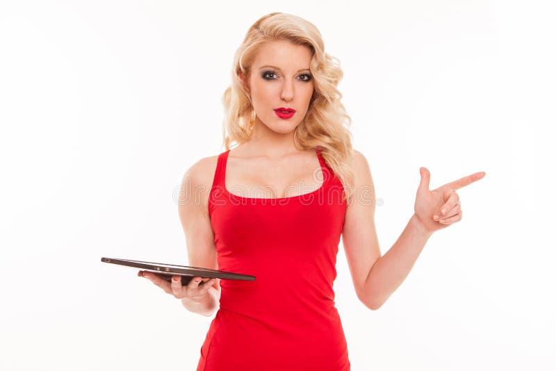拿着片剂comp的红色T恤杉的美丽的年轻白肤金发的妇女 免版税库存图片