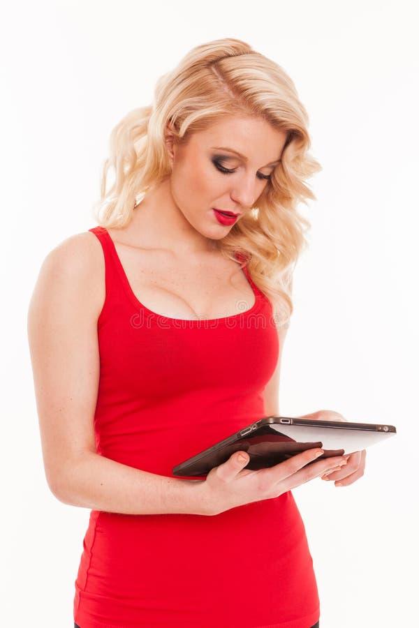 拿着片剂comp的红色T恤杉的美丽的年轻白肤金发的妇女 库存照片