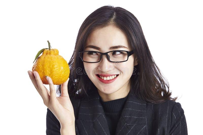 拿着牙买加丑橘的年轻亚裔女商人 免版税库存图片