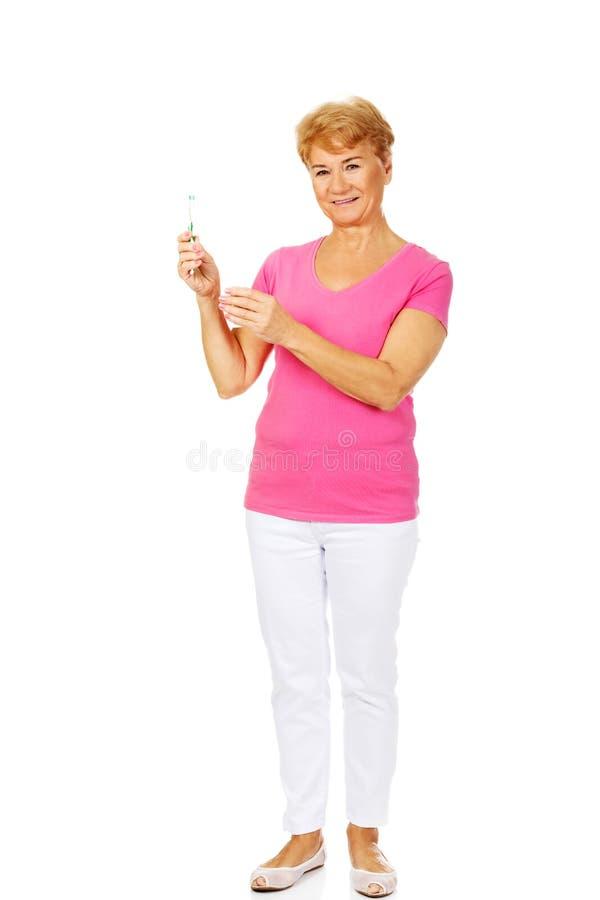 拿着牙膏和牙刷的微笑的资深妇女 免版税库存照片