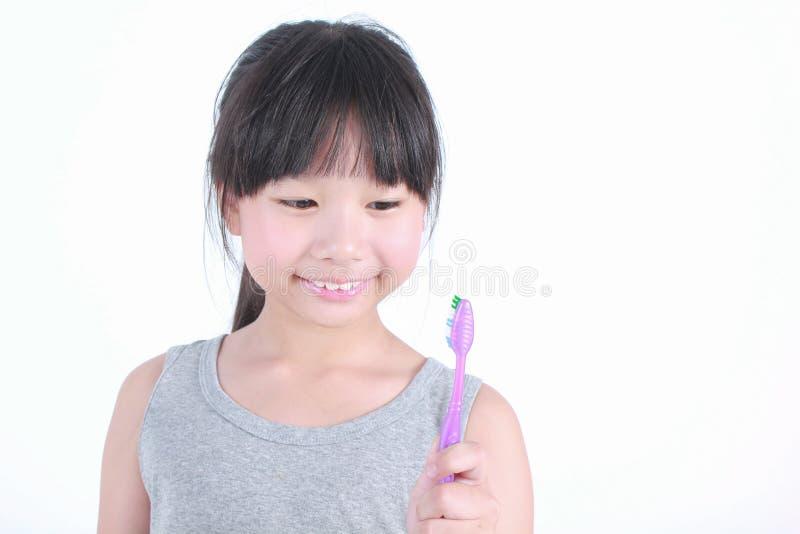 拿着牙膏的年轻逗人喜爱的矮小的亚裔女孩画象  库存图片
