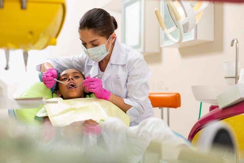 拿着牙齿仪器的被集中的严肃的中年女性医生 免版税库存图片