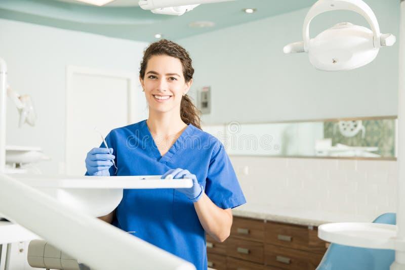 拿着牙齿卡佛的微笑的牙医画象在诊所 免版税库存图片
