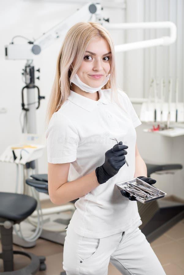 拿着牙齿工具的年轻可爱的女性牙医画象在现代牙齿办公室 库存图片