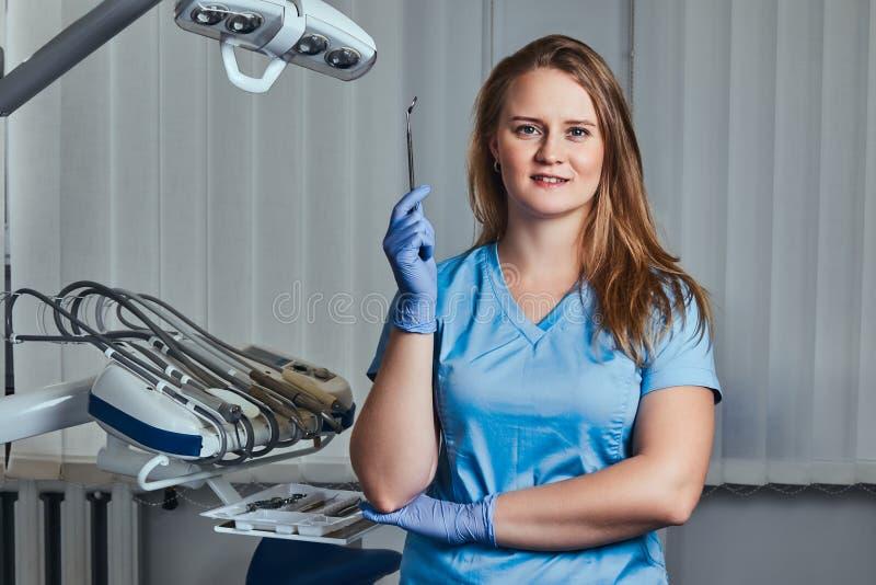 拿着牙齿镜子的微笑的女性牙医,当站立在她的牙医办公室时 免版税库存图片