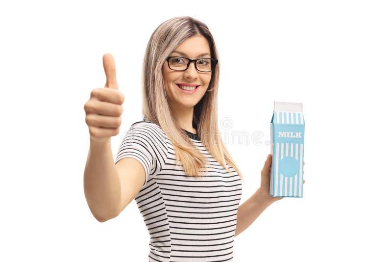 拿着牛奶纸盒和做赞许标志的少妇 免版税图库摄影