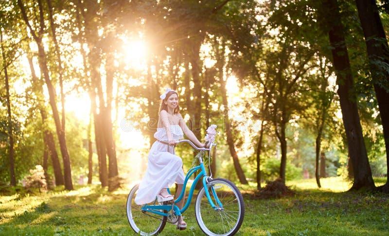 拿着牡丹的白色礼服的美丽的女孩,当乘坐蓝色自行车下来美丽的晴朗的公园胡同时 免版税库存图片