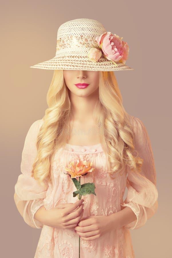 拿着牡丹花,女孩桃红色礼服的时尚草帽的妇女 免版税库存照片
