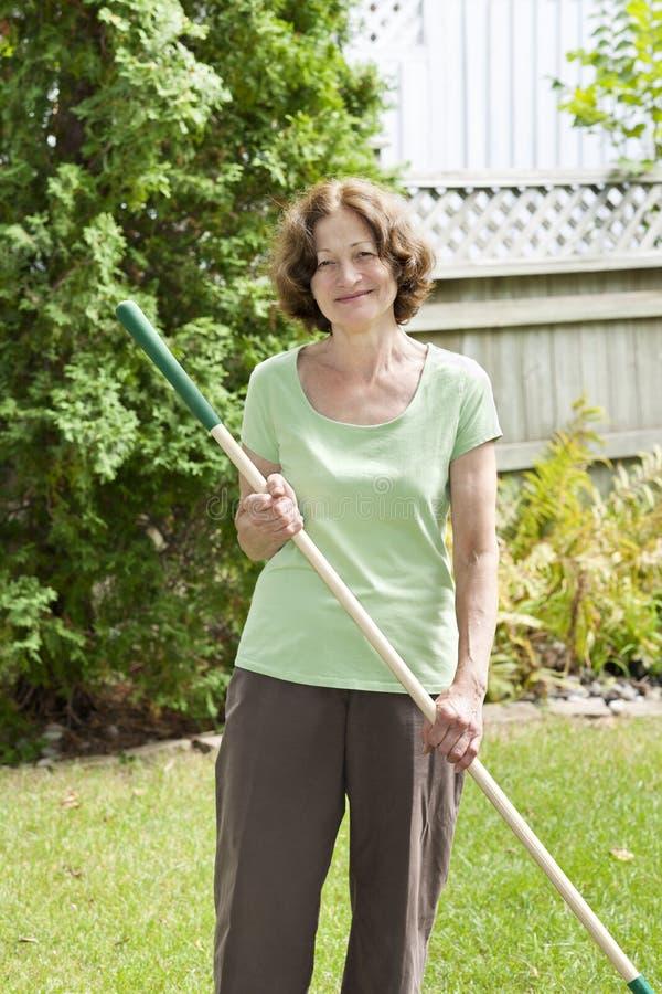 拿着犁耙的资深妇女 免版税库存照片
