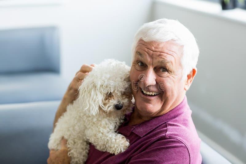 拿着狗的老人 免版税库存图片