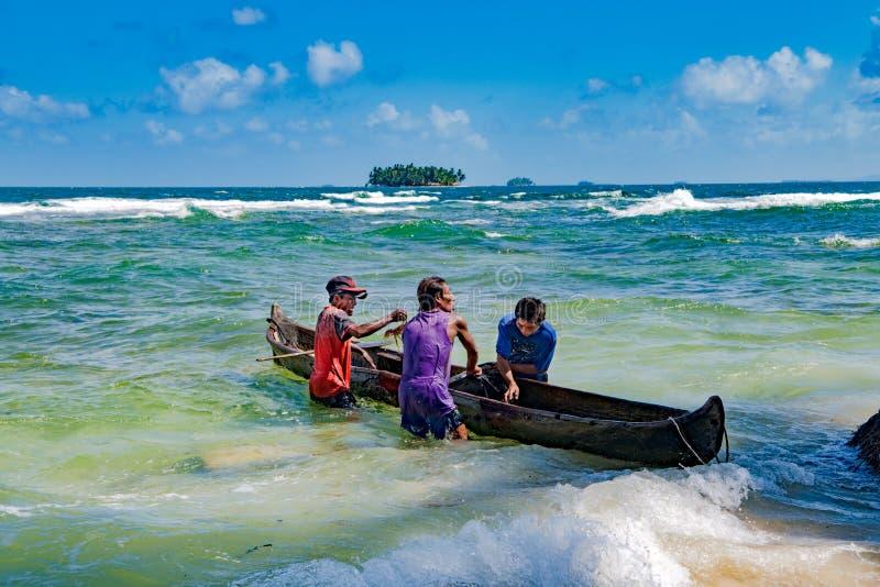 拿着独木舟的渔夫拿来龙虾和螃蟹在小海岛上在加勒比海 免版税库存照片
