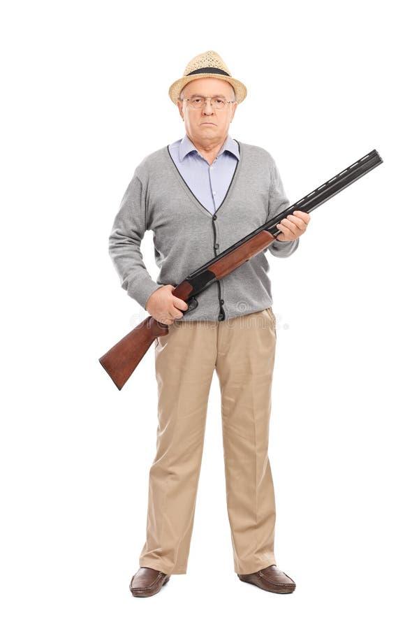 拿着猎枪的严肃的资深绅士 免版税库存照片