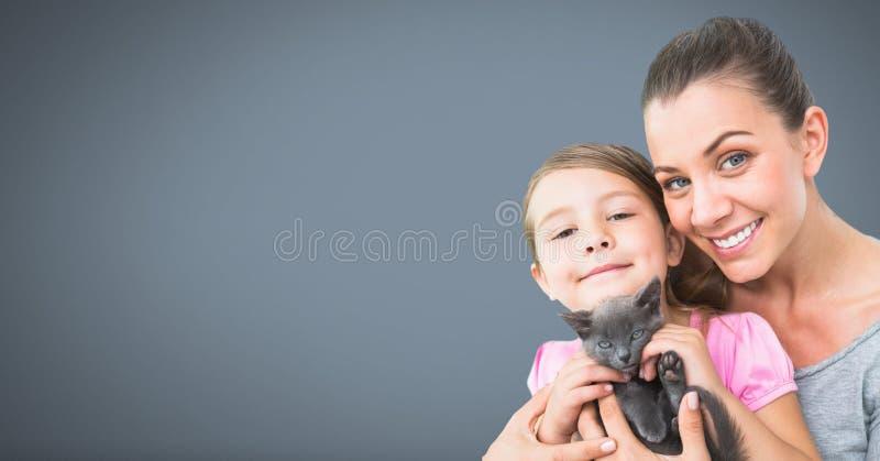 拿着猫有灰色背景的母亲和女儿 库存例证