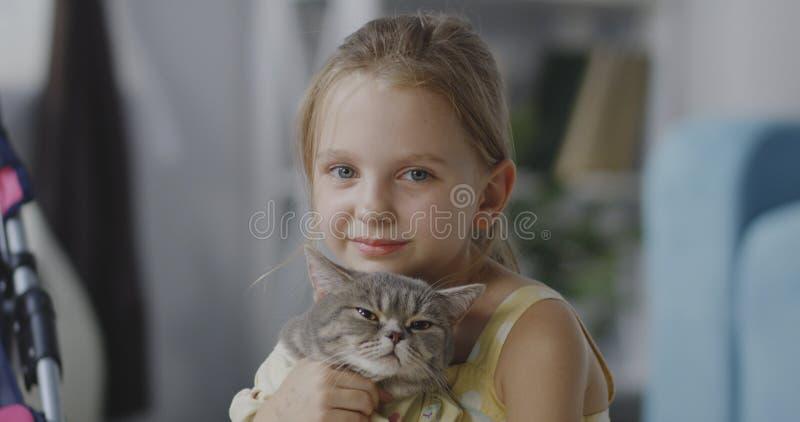 拿着猫的女孩 库存图片