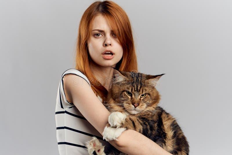 拿着猫的美丽的妇女 库存图片