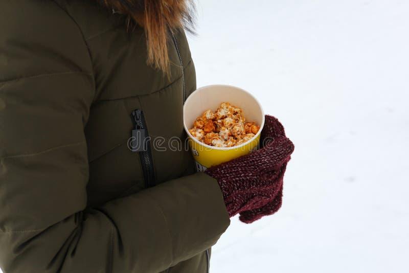 拿着玉米花的年轻女人在冬天,在手套 免版税图库摄影